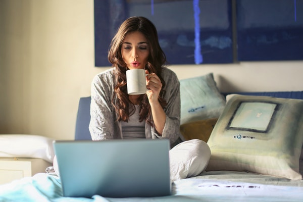 Adult lady in bed with laptop while drinking coffee